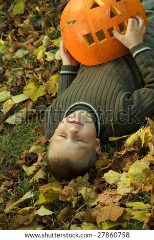 Laying little boy with halloween pumpkin - stock photo