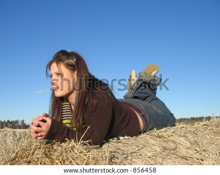 Laying on hay roll, in thought. - stock photo