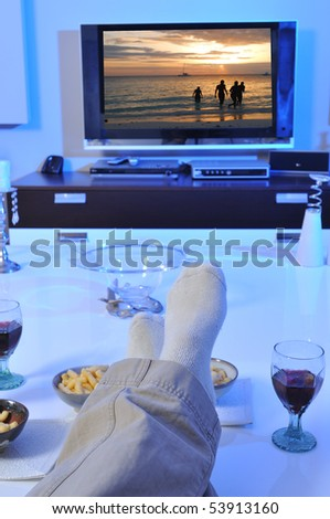 Laying on sofa and watching tv - stock photo