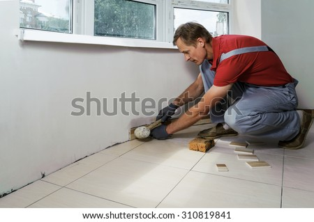 Laying the tiles. Tiler knocks a rubber mallet - stock photo