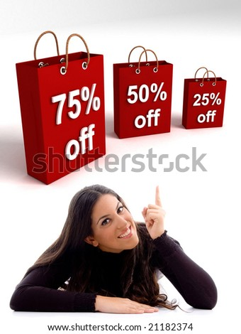 laying young woman pointing at the  three dimensional shopping bags - stock photo