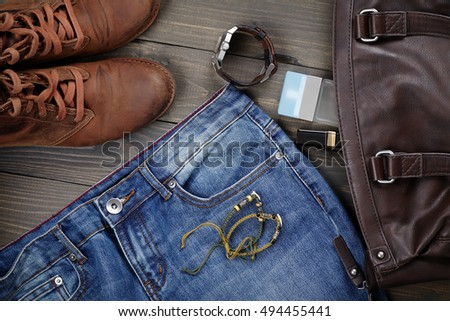 layout fashionable clothes and accessories from the top view, on a wooden board