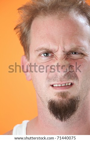 Lazy Caucasian male with goatee expressing his disgust - stock photo