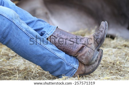 Lazy Cowboy leather boots and pants in blue jeans in the stable of bulls - stock photo