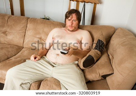Lazy fat man watching Tv while on the couch - stock photo