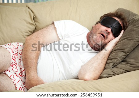 Lazy man at home in his underwear, sleeping on the couch and snoring.   - stock photo