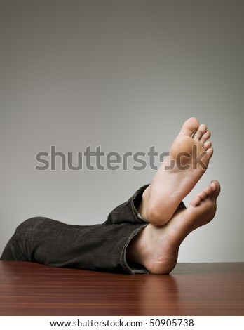 Lazy man with his feet at the table - stock photo
