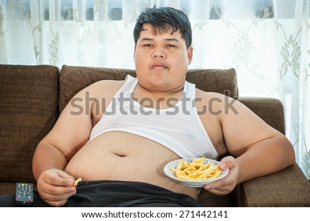 Lazy overweight asian male sitting with fast food on couch and watching television - stock photo