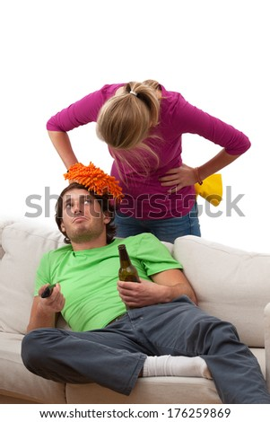 Lazy partner is sitting on the couch and drinking beer  - stock photo