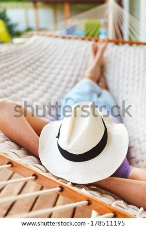 Lazy time. Man in hat in a hammock on a summer day - stock photo