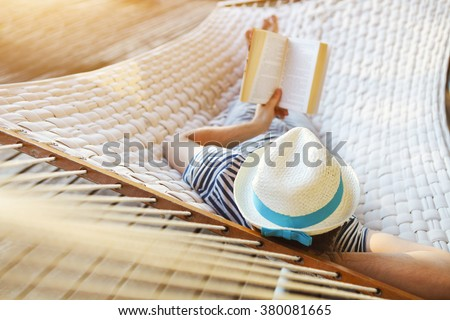 Lazy time. Man in hat in a hammock with book on a summer day - stock photo