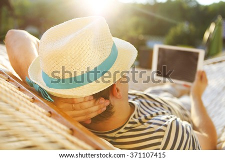 Lazy time. Man in hat in a hammock with tablet computer on a summer day - stock photo