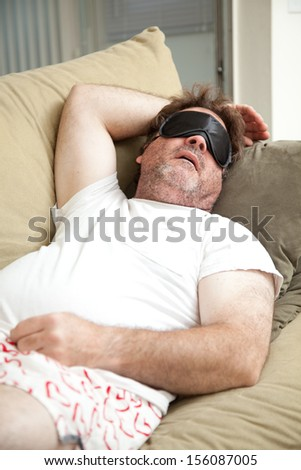 Lazy, unemployed man asleep on the couch, unshaven and in his underwear.   - stock photo