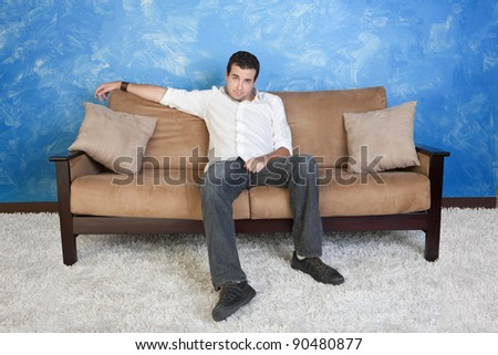 Lazy young Caucasian man sits in middle of couch - stock photo
