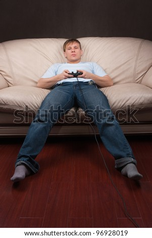 lazy young man playing video games on gray background