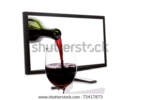 LCD computer monitor with red wine pouring into a glass while emerging from the screen. - stock photo