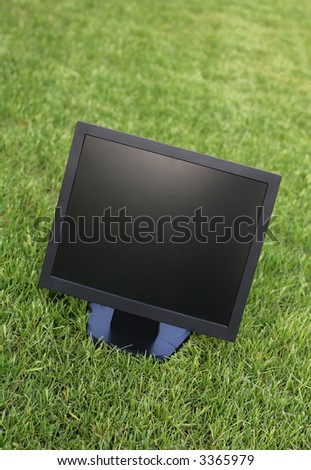 LCD computer screen on the green grass - stock photo