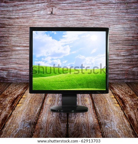 LCD monitor on wood floor and wall - stock photo