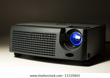 LCD projector in darkness with light on - stock photo