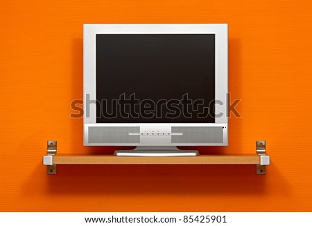 LCD TV against orange wall - stock photo