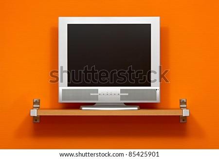 LCD TV against orange wall - stock photo