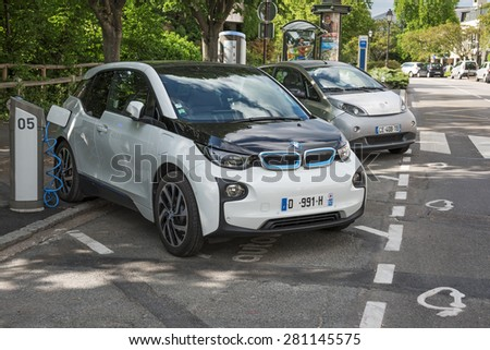 LE CHESNAY, FRANCE - MAI 25, 2015: Electric car BMW I3 charging its batteries on a parking for Cars Autolib. Autolib is a french carsharing service of electric car - stock photo