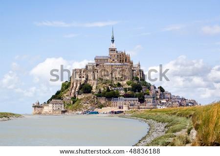 Le Mont Saint Michel on horizon under blue sky, Normandie, France - stock photo