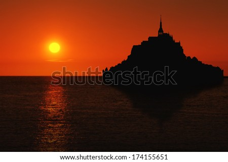 Le Mont Saint Michel silhouette with reflection in Normandy, France at sunset - stock photo