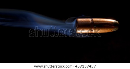 Lead bullet with a copper plate on black with smoke behind