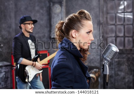 Lead singer stands at microphone in studio - stock photo