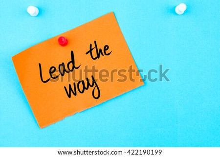 Lead The Way written on orange paper note pinned on cork board with white thumbtack, copy space available
