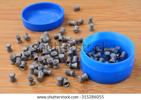 Leaden air rifle shots and blue plastic box on wooden background - stock photo