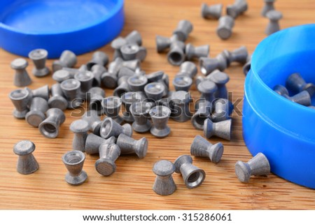 Leaden air rifle shots and blue plastic box on wooden background, close up view - stock photo