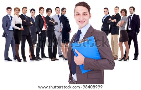 Leader holding a clipboard with business team behind, isolated on white. young business man holding a clipboard in front of a large happy business team - stock photo