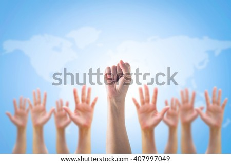 Leader's fist victory sign among blur hands crowd group: Many people blurred palms raising up upward on blue sky background map: World participation, leadership, volunteer concept  - stock photo