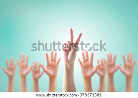 Leader's two fingers victory sign among blur hands crowd group:: Many people blurred palms raising up upward on vintage blue sky background: World participation, leadership, volunteer concept - stock photo