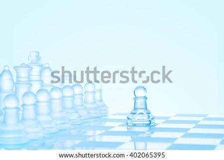 Leadership and bravery concept; an icy frosted single pawn staying against a full set of chess pieces on chessboard.