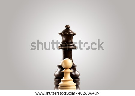 Leadership and bravery concept; white wooden single pawn staying against a black queen. - stock photo