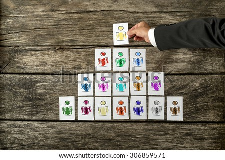Leadership and team management concept with a businessman arranging a series of hand-drawn cards depicting people into a pyramid and just about to place the last card at the pinnacle in place. - stock photo