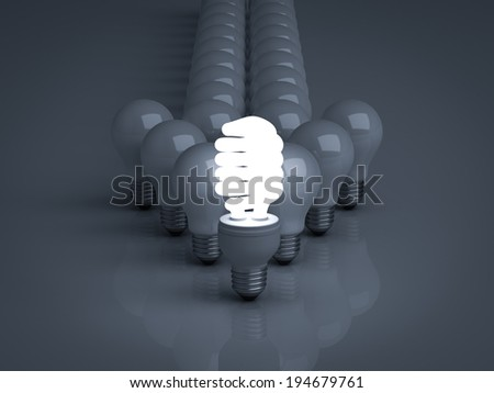 Leadership concept, One glowing Eco energy saving light bulb standing in front of unlit incandescent bulbs with reflection on dark background - stock photo