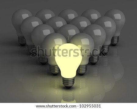 Leadership concept, One glowing light bulb standing in front of unlit incandescent bulbs with reflection on dark background - stock photo