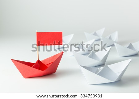 Leadership concept with red paper ship leading among white - stock photo