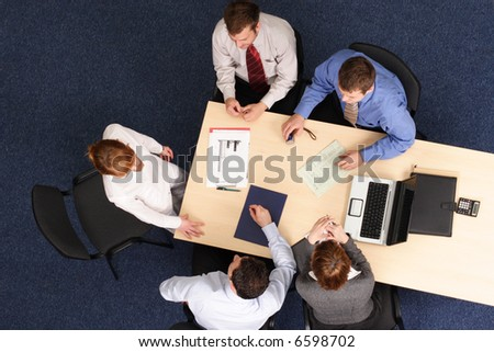 leadership -five business people meeting - Businesspeople gathered around a table for a meeting, brainstorming. Aerial shot taken from directly above the table. - stock photo