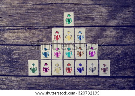 Leadership, human resources and team management concept with a series of hand-drawn cards depicting people structured into a pyramid over rustic wooden boards. - stock photo