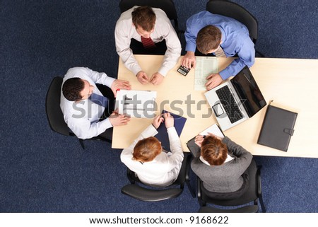 leadership - mentoring, five business people meeting - Businesspeople gathered around a table for a meeting, brainstorming. Aerial shot taken from directly above the table. - stock photo