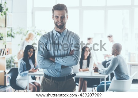 Leading my team to success! Handsome young businessman in smart casual wear keeping arms crossed and smiling while his colleagues working in the background   - stock photo