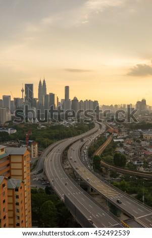 Leading road to Kuala Lumpur city skyline during golden sunset - stock photo