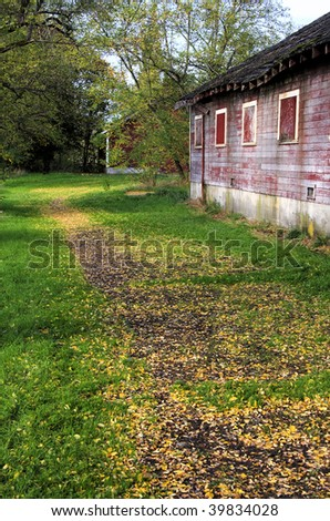 Leaf covered path around an old barn - stock photo