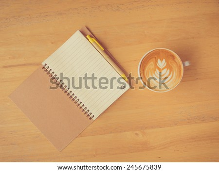 Leaf latte art coffee and notebook with pen on wooden table (Vintage soft style) - stock photo