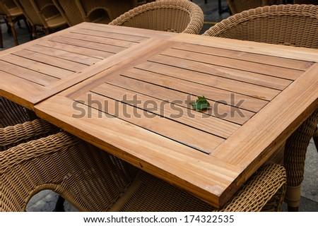 Leaf on the empty table on the terrace of open air cafe. Wooden tables and wicker armchairs.  - stock photo